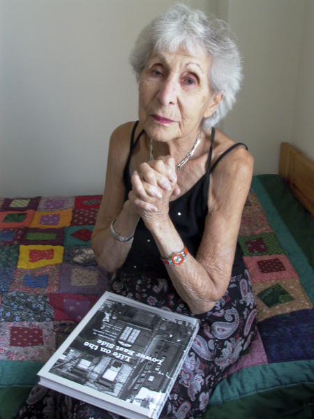 Rebecca Lepkoff at home with her first published book and her handmade quilt. Photo by Ellen Wallenstein.
