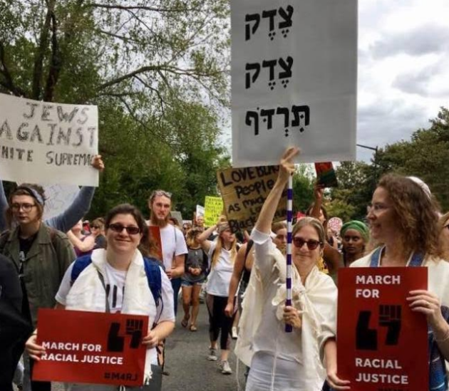 Photo credit: Susan Wasserkrug. The red signs was created by Lynna Schaefer. Carrying the red sign on the left: Rabbi Amber Powers. Carrying the Tsedek sign: Betsy Teutsch.  Carrying the red sign on the right, Lynna Schaefer
