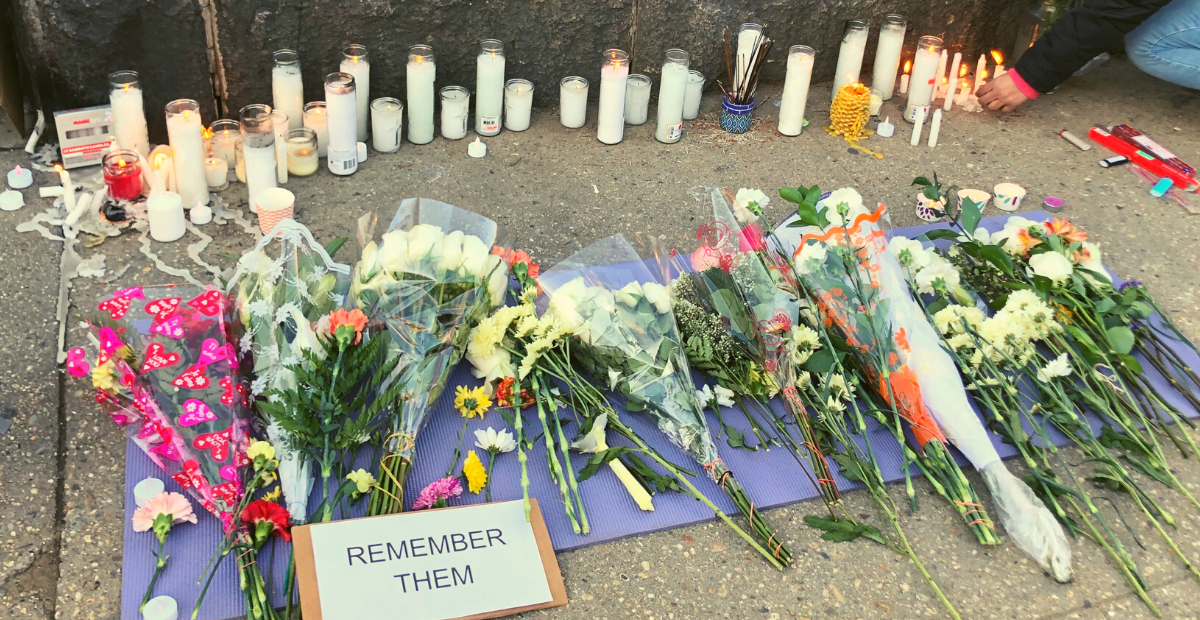 """Rows of lit candles and flowers with a sign that says, """"Remember Them."""""""