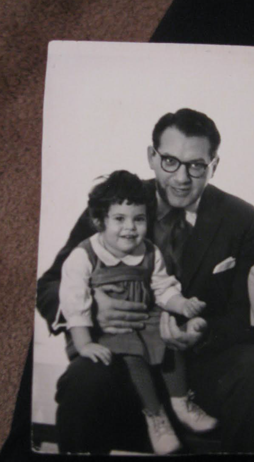 A father with a daughter in his lap; vintage photo.